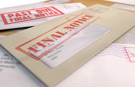 An envelope of overdue debt payments sits on a table after a divorce
