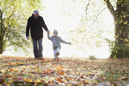 Grandfather walking outdoors with grandson in autumn after divorce agreement
